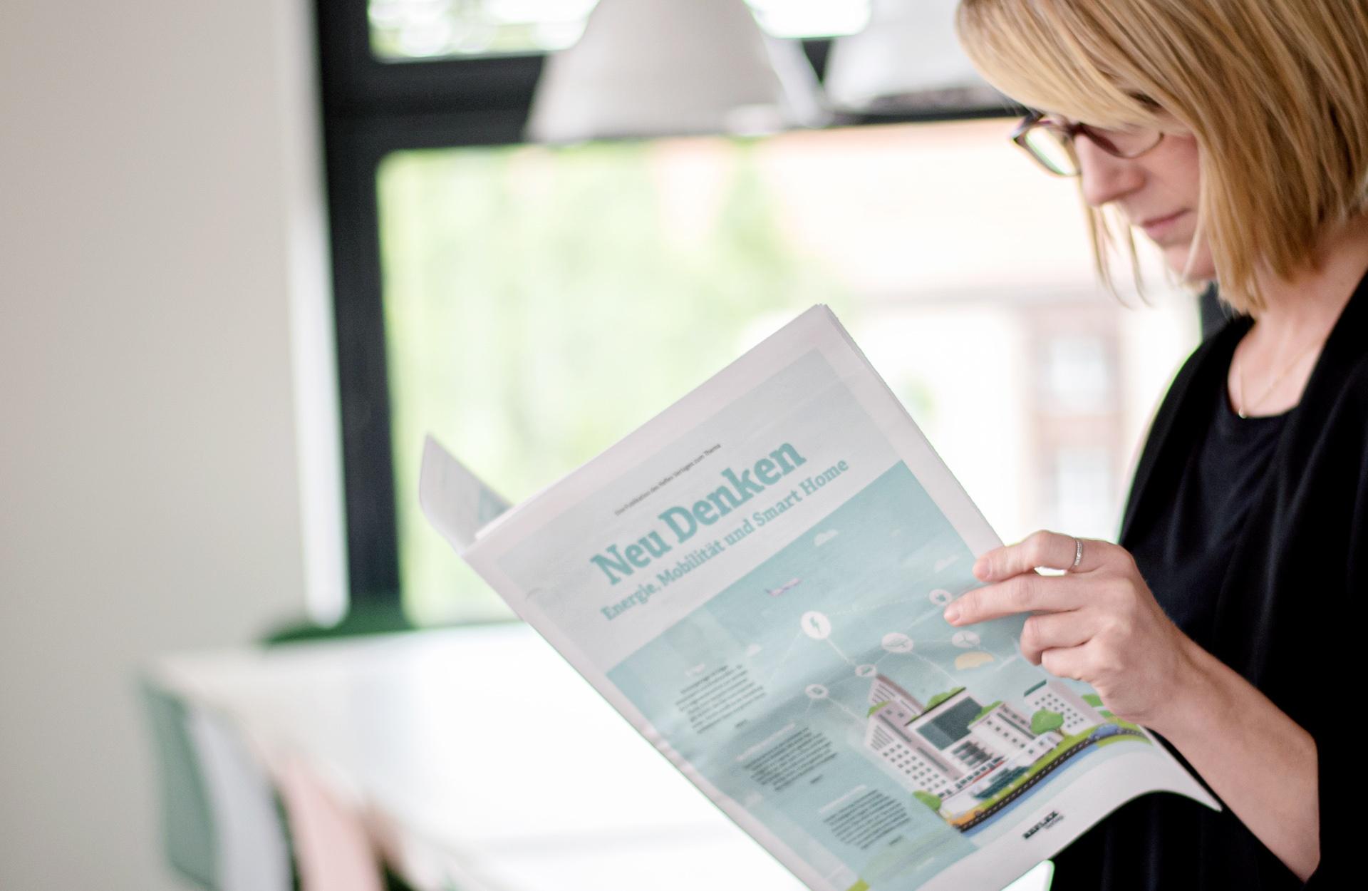 Mitarbeiterin liest unseren Artikel in der Neu Denken: Energie, Mobilität und Smart Home.