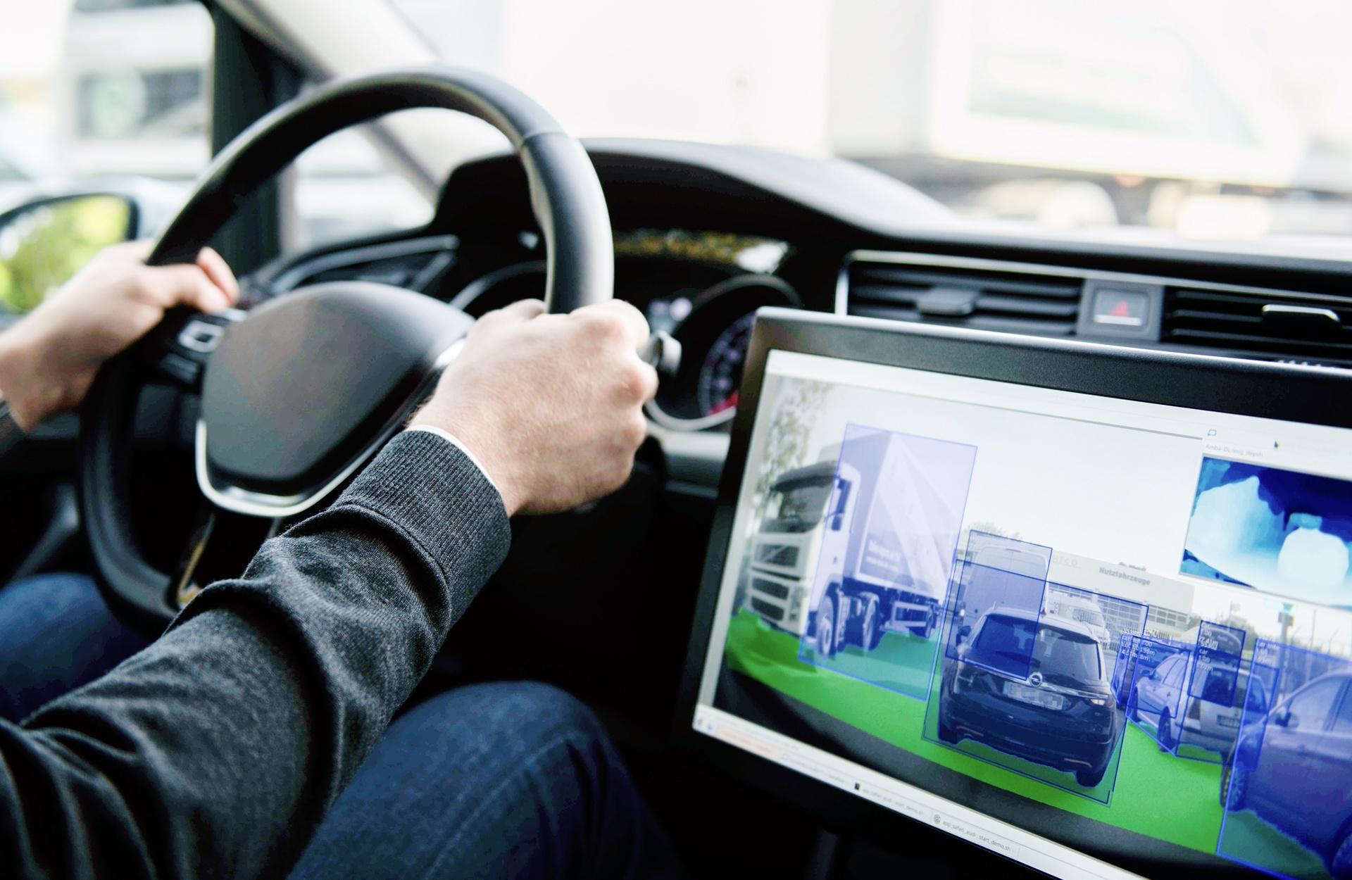 Der Bildschirm neben dem Lenkrad zeigt die kamerabasierte Detektion von Fahrzeugen und Straßenfläche im Stadtverkehr.